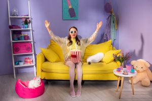 Young woman posing as doll with popcorn in 3d glasses on yellow